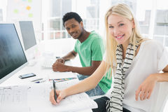 Artist drawing something on paper besides colleague at office Stock Photos