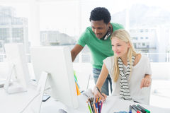 Artist drawing something on paper with colleague at office Royalty Free Stock Photo