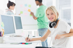 Artist drawing something on paper with colleagues behind at office Stock Photography