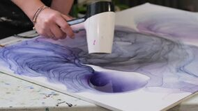 Artist draws abstraction with ink. hair dryer blurs mascara creating an abstract drawing