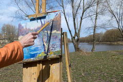 Artist draws a brush and oil paints spring landscape. With a lake and trees stock image