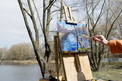 Artist draws a brush and oil paints spring landscape. With a lake and trees stock photo