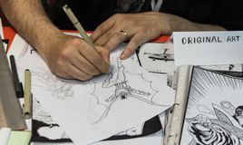 The artist draws a comic strip. Athens, Greece - April 16, 2016: Exhibition Comics, the artist draws on pencil a comic strip royalty free stock photos