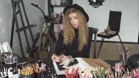Artist draws at the desk. Talented artist drawing a picture of boy at the desk full of coloured pencils, wearing black outfit and cool hat as working in the stock video footage