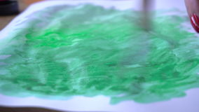 The artist draws a divorce on paper green paint and a brush stock video