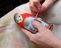 The artist draws a doll-matryoshka. Hand closeup stock photo