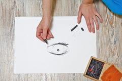 The artist draws the eye of coal. Royalty Free Stock Photos