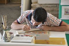 Artist draws paint picture for souvenir. Bukhara, Uzbekistan - August 5, 2015: School of Oriental arts. A young painter working on his new painting Royalty Free Stock Images