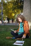 The artist draws in park. The girl sits on a grass and draws paints Royalty Free Stock Image