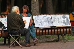 Artist draws a portrait of a woman in the city park of Minsk. Minsk, Belarus - August 09, 2013: Artist draws a portrait of a woman in the city park of Minsk stock image