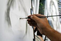 The artist draws a portrait of a woman. Artist on the streets draws on the easel the portrait of a woman Stock Photos