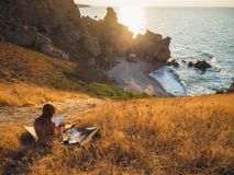 The artist draws the sea, Rus sea bay. Downstairs is her tent royalty free stock image