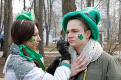 Artist draws a Shamrock on man`s face at the St. Patrick`s Day Parade in the park Sokolniki in Moscow Stock Photography
