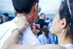 The artist draws a temporary tattoo on the guy`s neck with cosmetic pencil. The artist draws a temporary tattoo on the guy`s neck. Photo taken at the festival of royalty free stock photo