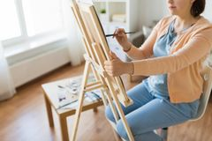 Artist with easel and brush painting at art studio. Fine art, creativity and people concept - close up of artist with easel and paintbrush painting at studio stock photos