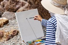 The artist with an easel. And colorful paints royalty free stock photos