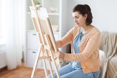 Artist with easel drawing picture at art studio. Art, creativity and people concept - artist with easel drawing picture at studio royalty free stock photos