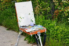 Artist easel with paints standing outdoors Royalty Free Stock Photography