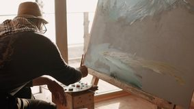 Artist is engaged in drawing oil paints by brush on canvas which stands on easel. The adult artist is engaged in professional drawing by oil paints, he puts a stock footage