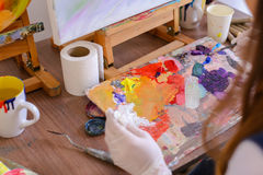 Artist extrudes paint from tubes on  palette for mixing colors t Royalty Free Stock Image