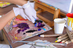 Artist extrudes paint from tubes on  palette for mixing colors t Royalty Free Stock Photography