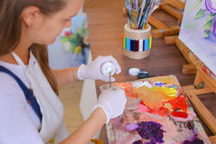 Artist extrudes paint from tubes on  palette for mixing colors t Stock Photo