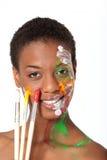 Artist in facepaint holding brushes Stock Photo