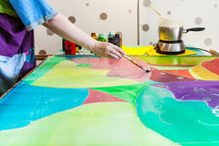 Artist gets second layer of paint on silk fabric Royalty Free Stock Photography