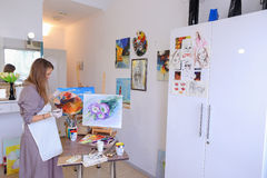 Artist Girl Holds Brush in Hand And Draws on Canvas, Picks up Ph Royalty Free Stock Photography