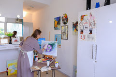 Artist Girl Holds Brush in Hand And Draws on Canvas, Picks up Ph Royalty Free Stock Photos
