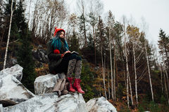 Artist girl painting sitting on the rocks at the cliff, notepad. Wonderful fall view stock images