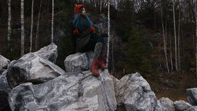 Artist girl painting sitting on the rocks at the cliff, notepad. Wonderful fall view stock video