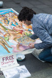 Artist give away drawings for free. SYDNEY, AUSTRALIA - SEPTEMBER 14, 2014: An unknown man paints a very big fresco in the middle of Pitt Street. He is giving Stock Photo
