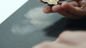 An artist grinds wooden craft on sandpaper.  stock video