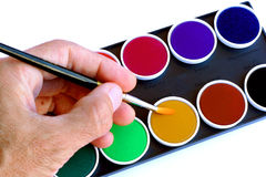 Artist hand. Holding paintbrush on watercolors Royalty Free Stock Photo