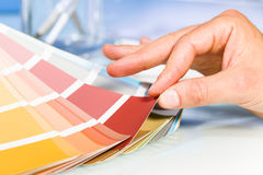 Artist hand browsing color samples in palette Stock Photos
