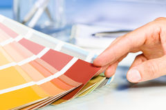 Artist hand browsing color samples in palette. Close up of Artist hand browsing color samples in palette in studio background stock image