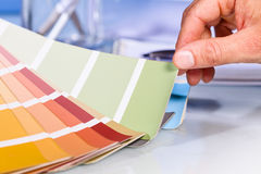 Artist hand browsing color samples in palette Royalty Free Stock Images