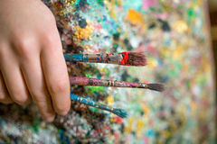 Artist hand holding paintbrush. Closeup of female artist hand holding paintbrush Royalty Free Stock Images