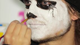 Artist hand painting man`s nose black at halloween stock video footage