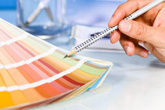 Artist hand pointing to color samples in palette Royalty Free Stock Images