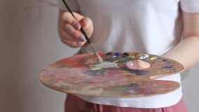 Artist hands with brush mixing colors on palette close up. Art, creativity, hobby. Artist hands with brush mixing colors on palette close up. Art, creativity stock footage