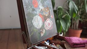 Artist hands with brush painting picture of flowers close up. Art, creativity, hobby concept. Close up on artist hands with brush painting flowers picture on an stock video footage