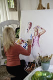 Artist in her fifties painting Royalty Free Stock Photos