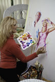 Artist in her fifties painting. Beautiful blond artist in her fifties painting on canvas Stock Photography