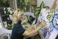 Artist in her fifties painting Royalty Free Stock Photo
