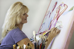 Artist in her fifties painting on canvas. Beautiful blond artist in her fifties painting on canvas in her studio royalty free stock photography