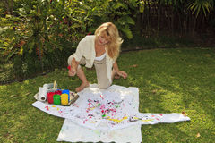 Artist in her fifties painting a shirt Royalty Free Stock Photo
