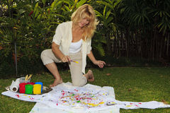 Artist in her fifties painting a shirt Stock Photo