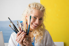 Artist in her studio holding paint brushes Royalty Free Stock Photography